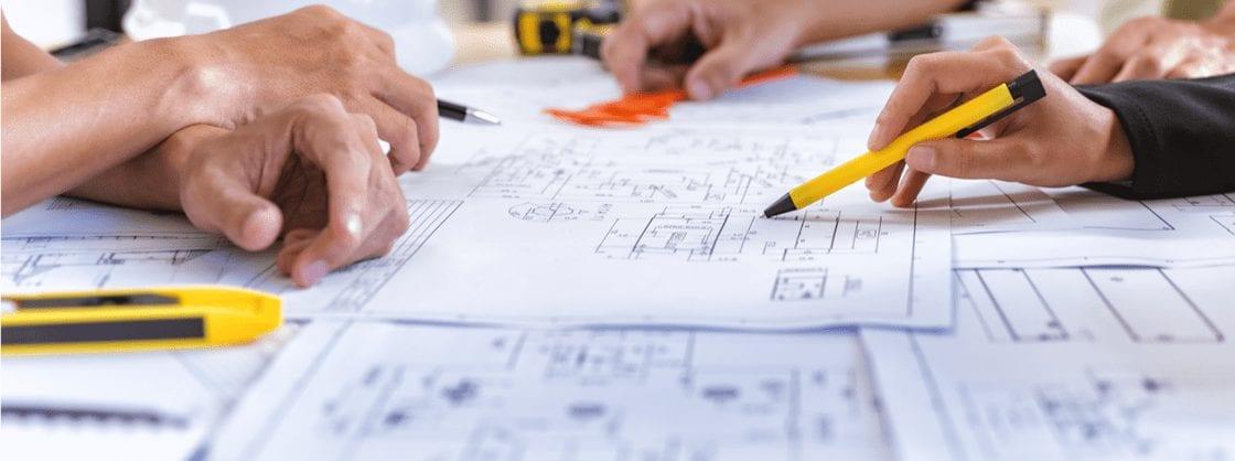 mãos segurando canetas sobre plantas baixas de um projeto